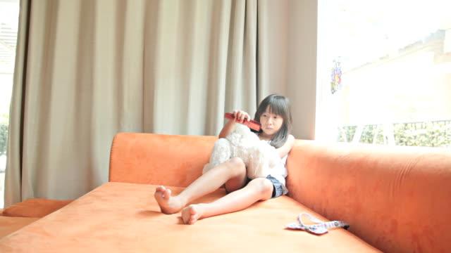 hd :dolly ガールのテディベアオレンジ色のソファーに座っています。 - ぬいぐるみ点の映像素材/bロール