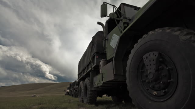 dollying time-lapse of a stationary military convoy truck. - militärisches trainingslager stock-videos und b-roll-filmmaterial