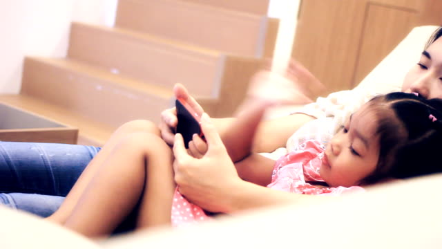 HD dolly:Mother and daughter spending time together and playing games using telephone on bed.