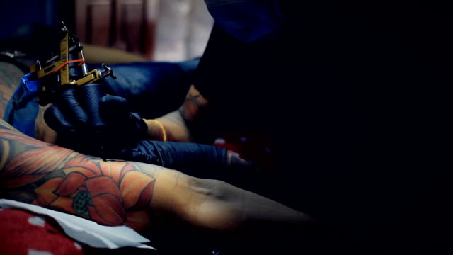 HD dolly:Tattoo Artist Tattooing an Elaborate Sleeve Design on Man's Arm
