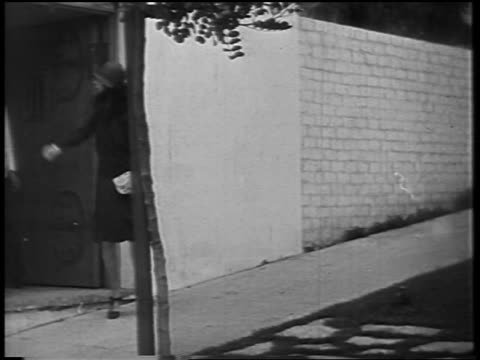 stockvideo's en b-roll-footage met dolores del rio walking to limousine where black chauffeur waits / newsreel - 1928