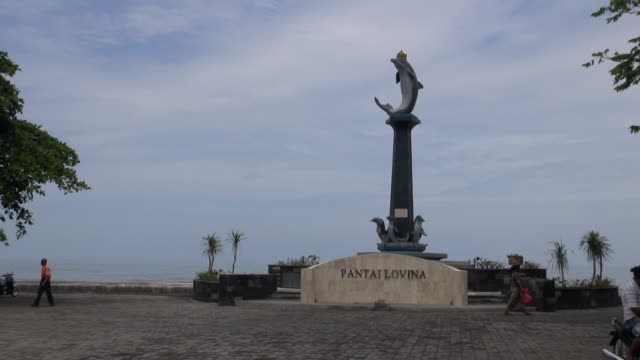 WS of dolphin monument on seafront at the tourist resort of Lovina
