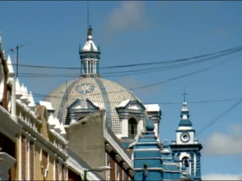 Dome of blue cathedral / tilt down cathedral to street with traffic and pedestrians / Puebla, Mexico