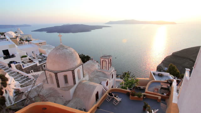 dome of the local church and the white washed houses of thira at sunset overlooking the aegean sea on the island of santorini, greece, europe - santorini stock videos & royalty-free footage
