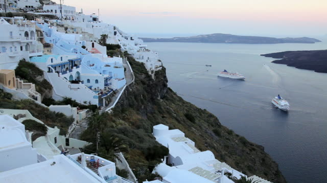 Dome of the local church and the white washed houses of Thira overlooking Cruise ships and the Aegean Sea on the Island of Santorini, Greece, Europe
