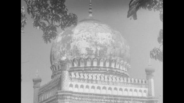 EXT dome of the Qutb Shahi Tombs with tree branches in foreground / VS ruins of Golkonda fort / Note exact day not known