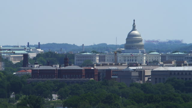 dome of the us capitol building with smithsonian castle at left. shot in 2012. - smithsonian institution stock videos & royalty-free footage
