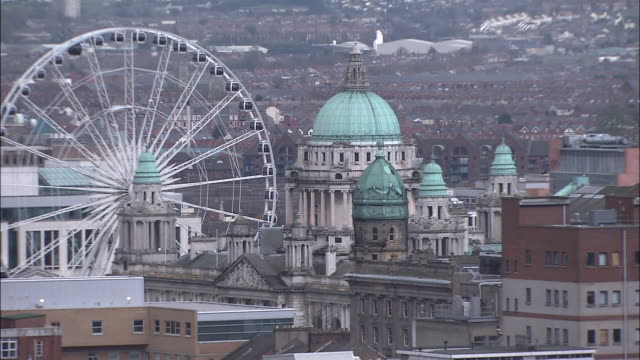 vídeos de stock e filmes b-roll de domed buildings and other buildings of belfast surround a huge ferris wheel. - belfast