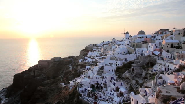 Domed white washed churches of Oia at Sunset with a view overlooking the Aegean Sea on the Island of Santorini, Greece, Europe