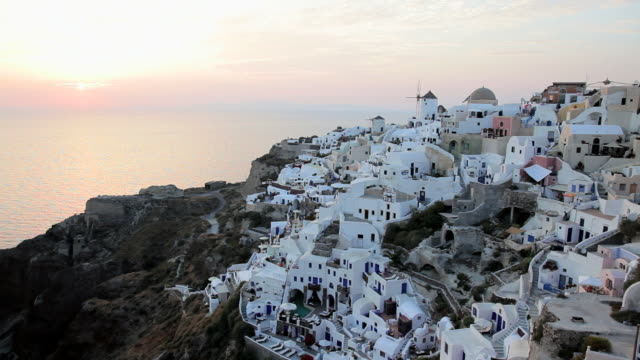domed white washed churches of oia at sunset with a view overlooking the aegean sea on the island of santorini, greece, europe - 白しっくい塗点の映像素材/bロール