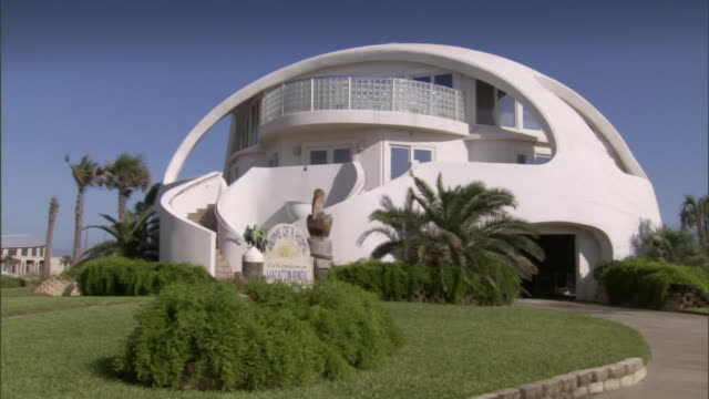 a dome-shaped home has a beautifully landscaped yard. - kuppeldach oder kuppel stock-videos und b-roll-filmmaterial