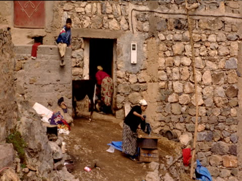 domestic scene in mountain village woman washing clothes child sitting on wall calf tethered by doorway - 牛車点の映像素材/bロール