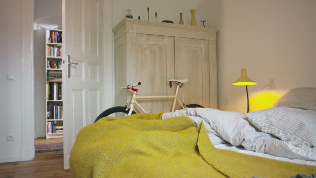 domestic stylish bedroom with single speed city bike - empty location - panning camera. - bedclothes stock videos & royalty-free footage