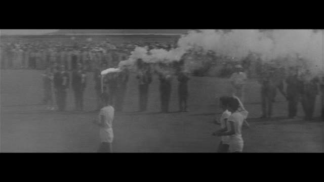 vídeos de stock e filmes b-roll de domestic torch relay starts/flame arrives at kagoshima airport first runner ritsuko takahashi takes off flame passed to second route miyazaki airport... - 1964