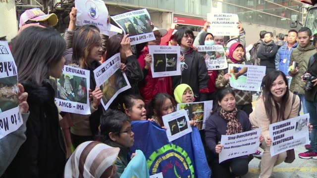domestic workers take to the streets of hong kong demanding justice for an indonesian maid allegedly tortured by her employers and better protection... - fordern stock-videos und b-roll-filmmaterial