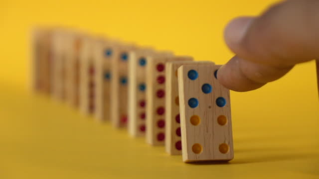 domino falling slow motion on yellow background - chain stock videos & royalty-free footage