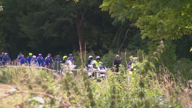 don lock road rage murder: funeral cortege with cyclists; gland: west sussex: worthing: ext cyclists gathered together on park area / police escort... - worthing点の映像素材/bロール