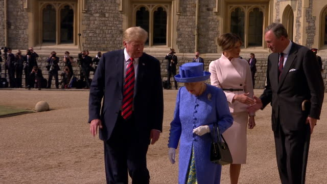Donald and Melania Trump walk with Queen Elizabeth II through the grounds of Windsor Castle on his first official visit to the UK