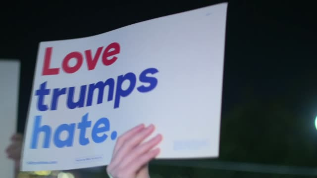 policy speculation washington dc immigrant protester addressing antitrump demonstration in street protester with placard love trumps hate protester... - politische wahl stock-videos und b-roll-filmmaterial