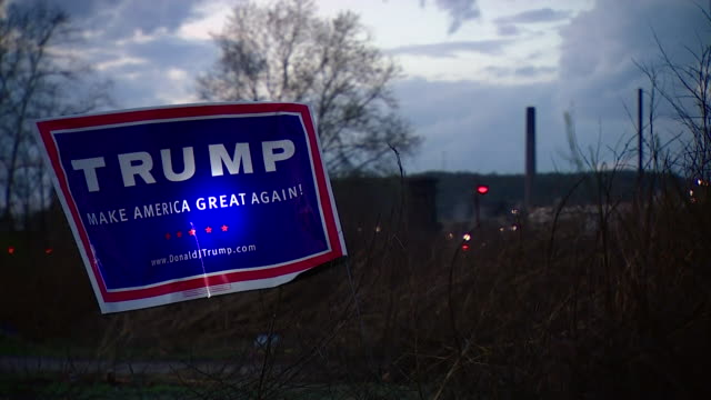 A Donald Trump sign next to a hedge with a steel meel in Indiana visible in the background
