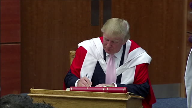 donald trump signs a book during a ceremony presenting him with an honorary degree from the robert gordon university scotland - ceremonial robe stock videos and b-roll footage