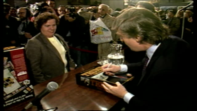 vídeos de stock, filmes e b-roll de donald trump signs his trump board game at fao schwarz - 1980 1989