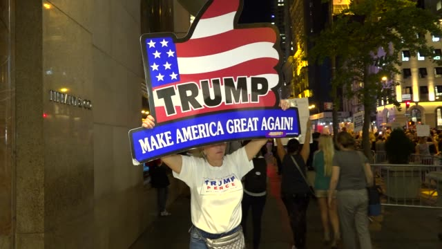 donald trump supporter holds protrump banner sign during antitrump rally / protesters gathered outside of trump tower on 5th avenue and dubbed the... - 2016 united states presidential election stock videos & royalty-free footage