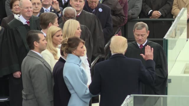 Donald Trump takes the oath of office to become the 45th President of the United States Chief Justice Roberts administers the oath Side shot from...