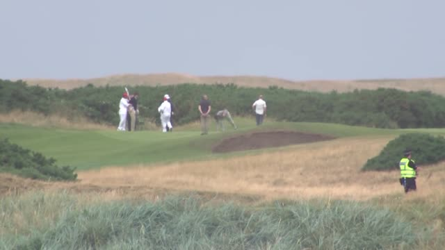 vidéos et rushes de trump plays golf at turnberry brief shot of protesters scotland turnberry ext various long shots of donald trump playing golf with his son eric trump... - terrain de golf