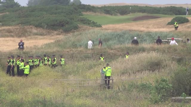 Trump plays golf at Turnberry brief shot of protesters SCOTLAND Turnberry EXT Various long shots of Donald Trump playing golf with his son Eric Trump...