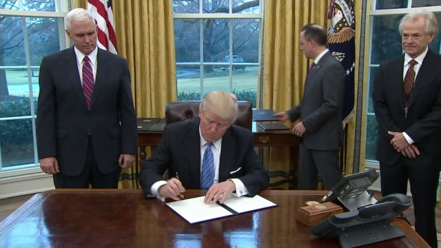 Donald Trump's immigration policy / Mexican border wall Washington DC The White House INT General view Donald Trump in Oval Office signing orders...