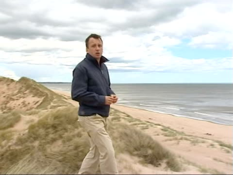 donald trump's plans for golf club threatened by wind farm proposals; scotland: aberdeenshire: reporter to camera wide shot sea and sandy beach... - golf links stock videos & royalty-free footage