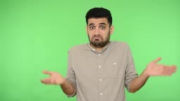 I don't know. Confused brunette man shrugging shoulders making questioning gesture., green background, chroma key