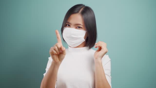 stockvideo's en b-roll-footage met raak je gezicht niet aan. aziatische vrouw die hygiënemasker draagt dat handeindeteken en zich geïsoleerd over blauwe achtergrond toont. concepten van de gezondheidszorg. 4k video. - vermijden
