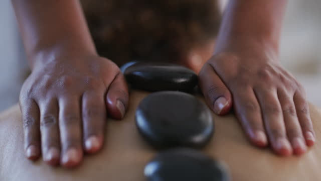 vídeos de stock e filmes b-roll de don't underestimate the power of the stone - spa treatment