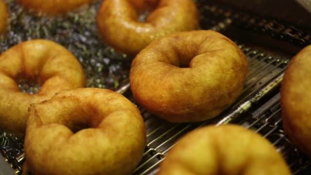 cu slo mo donuts coming out of oil onto rack/ johannesburg/ south africa - doughnut stock videos & royalty-free footage