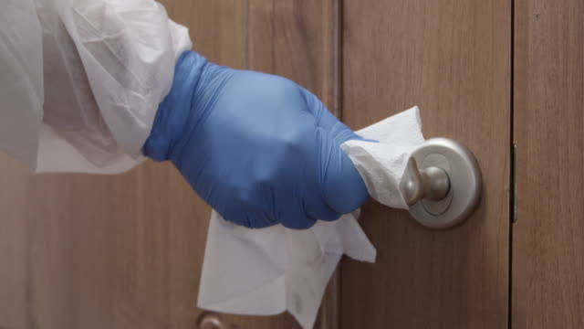door handle disinfecting with spray hand sanitizer and paper towel in gloves and protective suit from coronavirus covid-19 shot on red - wipe video transition stock videos & royalty-free footage