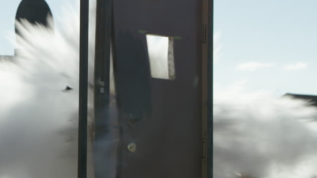 a door in a doorframe is blown open by explosives outdoors on a sunny day - explosion wall stock videos and b-roll footage