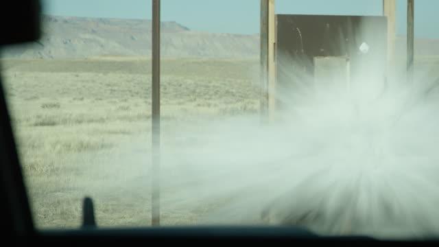stockvideo's en b-roll-footage met a door in a doorframe is blown open by explosives outdoors on a sunny day in a desert scene - springstof wapen