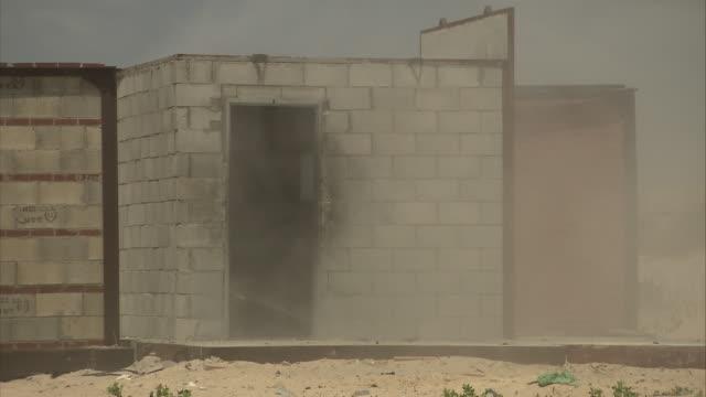 vidéos et rushes de a door is blown off a cinder block structure. - parpaing