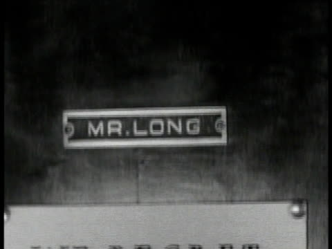 stockvideo's en b-roll-footage met door mr long's residence w/ note '...cannot receive visitors...' huey long rubbing face w/ hand. - 1933