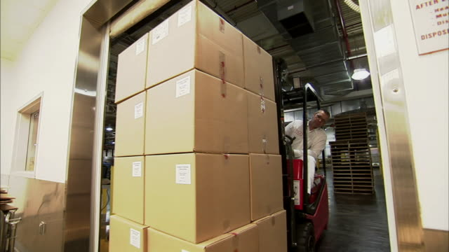 ms pan  door opening so that forklift can bring a load of boxes through/ forklift reversing through door/ new jersey - box container stock videos and b-roll footage