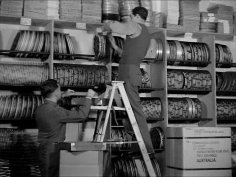 door 'overseas motion picture serviceny branch' soldiers on ladder in film vault handing film cans to soldier below soldier packing film box into... - newsreel stock videos & royalty-free footage