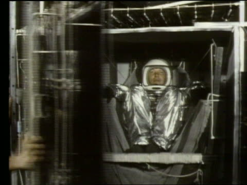 Door shutting on astronaut in compartment for space test