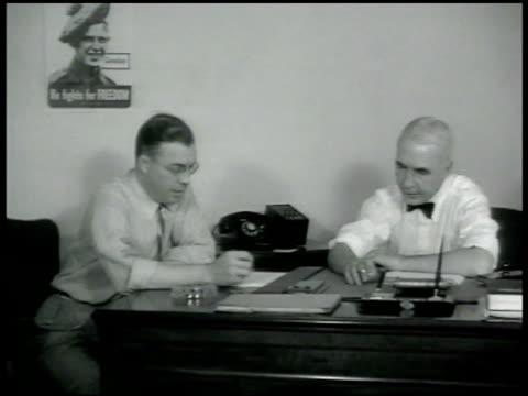 vidéos et rushes de door sign 'mr davis mr eisenhower' int office w/ director of war information elmer davis sitting at desk talking w/ unidentified man ms office of... - 1942