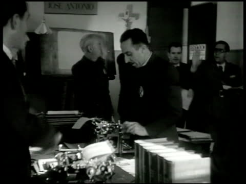 door sign: 'redencion journal de los prisoneros' men in room working on typewriters standing saluting to males entering room. vs male removing folded... - censorship stock videos & royalty-free footage