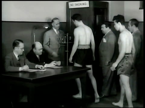 door sign 'weighingin room boxers only' int room w/ boxers dressed in boxing trunks being weighed boxer handing card to men at table man weighing... - card table stock videos & royalty-free footage