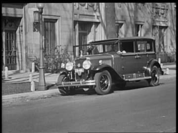 stockvideo's en b-roll-footage met b/w 1928 doorman holding door of cadillac open for woman  / industrial - 1928