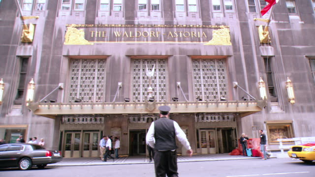 la doorman in uniform crossing park avenue to the waldorf-astoria hotel entrance, with pedestrians walking around / new york city, new york, united states - waldorf astoria stock videos and b-roll footage