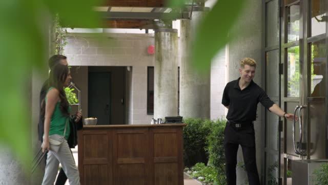 vídeos y material grabado en eventos de stock de doorman opening door for guests - entrada